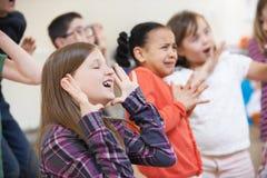 Grupp av barn som tillsammans tycker om dramagrupp royaltyfri fotografi