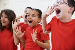 Grupp av barn som tillsammans tycker om dramagrupp Arkivbild