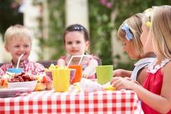 Grupp av barn som tycker om den utomhus- Teadeltagaren Fotografering för Bildbyråer