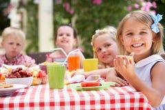 Grupp av barn som tycker om den utomhus- Teadeltagaren Royaltyfria Foton