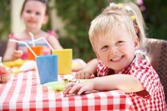 Grupp av barn som tycker om den utomhus- Teadeltagaren Royaltyfri Bild