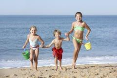 Grupp av barn som tycker om strandferie Arkivfoto