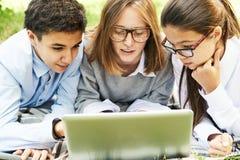 Grupp av barn som utomhus bläddrar internet arkivfoton