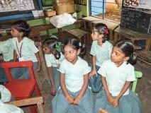 Grupp av barnvänklasskompisar som inomhus studerar sammanträde på stolar på skolan Skolaungar som tycker om kamratskap som är lyc arkivbilder