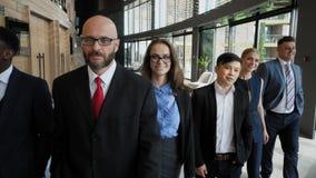 Grupp av blandras- affärsfolk som går till och med kontor in mot kamera långsam rörelse stock video