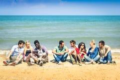 Grupp av blandras- bästa vän som talar på stranden arkivbilder