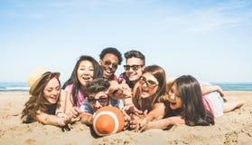 Grupp av blandras- lyckliga vänner som har gyckel som spelar sportbeac royaltyfria bilder