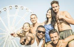Grupp av blandras- lyckliga vänner som tar selfie och har gyckel arkivfoton