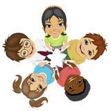 Grupp av blandras- ungar i en cirkel som ser upp rymma deras händer tillsammans Arkivbild