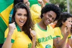 Grupp av brasilianska fotbollfans för bifall med flaggan av Brasilien arkivbild
