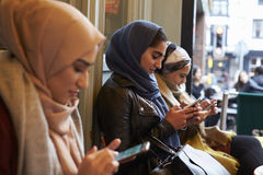 Grupp av brittiska muslimska kvinnor som smsar den utvändiga coffee shop Arkivfoton