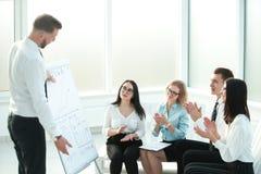 Grupp av businesspeople som appl?derar h?nder under m?te av presentation arkivbilder