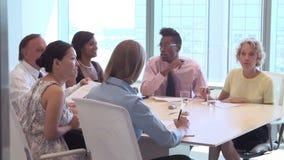 Grupp av Businesspeople som i regeringsställning möter runt om skrivbordet arkivfilmer