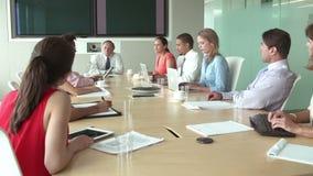 Grupp av Businesspeople som möter runt om styrelsetabellen lager videofilmer