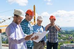 Grupp av byggmästare i Hardhats som möter på konstruktionsplatsen som bygger Team Working With Plan Engineer teamwork Arkivfoto