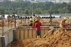 Grupp av byggnadsarbetare som fabricerar förstärkningstången Arkivfoto