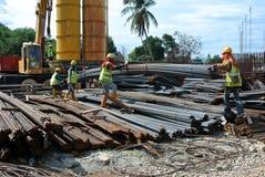 Grupp av byggnadsarbetare som lyfter packen av förstärkningstången genom att använda den mobila kranen Royaltyfri Foto