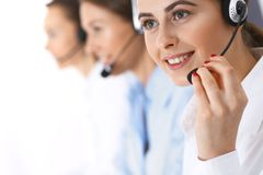 Grupp av callcenteroperatörer på arbete Fokus på den härliga affärskvinnan i hörlurar med mikrofon fotografering för bildbyråer