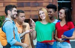 Grupp av caucasian och latin- och afrikansk amerikanstudenter som talar om läxa royaltyfri bild