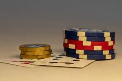 Grupp av chiper som lägger ner på tabellen med mynt och kort i bakgrunden Kasino och spelabegrepp royaltyfri bild