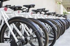 Grupp av cyklar i parkering i staden Arkivbilder
