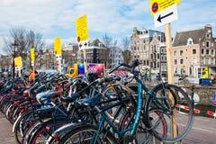 Grupp av cyklar som parkeras bredvid kanalen på det gamla centrala området i Amsterdam royaltyfri bild