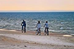 Grupp av cyklister som rider cyklar längs sjösidan i aftonen Arkivbilder