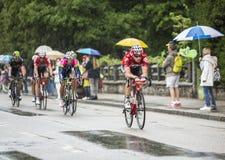 Grupp av cyklister som rider i regnet Arkivbild