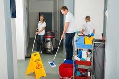 Grupp av dörrvakter som gör ren golvet i korridor arkivbild