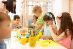 Grupp av dagisbarn som spelar med plasticine eller deg Små ungar har en gyckel samman med färgrikt modellera arkivbilder