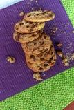 Grupp av declicious kakor med chokladgnistor på purpurfärgad och grön bordduk med stycken av galllette royaltyfri foto