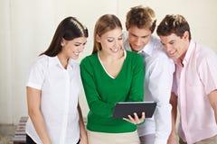 Grupp av deltagare som ser tableten Arkivbilder
