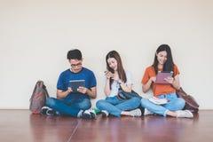 Grupp av den asiatiska h?gskolestudenten som anv?nder minnestavlan och mobiltelefonen utanf?r klassrum Lycka och utbildning som l arkivbilder