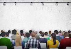 Grupp av den belägen mitt emot vita tegelstenväggen för olikt folk Arkivbild