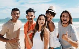 Grupp av den lyckliga latinska caucasianen och afrikansk amerikanmän och kvinna på stranden Royaltyfri Bild