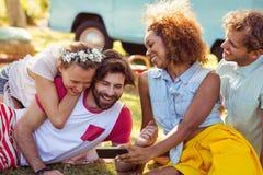 Grupp av den lyckliga vännen som använder mobiltelefonen royaltyfri fotografi