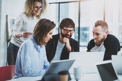 Grupp av den unga coworkersidékläckningprocessen på det soliga kontoret suddighet bakgrund arkivfoton