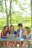 Grupp av den unga deltagaren som använder den utomhus- bärbar dator royaltyfria foton