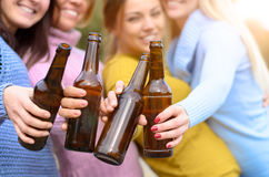 Grupp av den unga kvinnan som rostar med flaskan av öl Arkivfoton