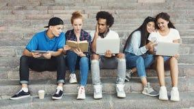 Grupp av den unga multietniska vännen som sitter på utomhus- trappa fotografering för bildbyråer
