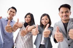 Grupp av den unga tummen för affärsfolk upp royaltyfria bilder