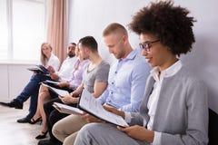 Grupp av den väntande på jobbintervjun för olikt folk arkivfoton