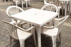 Grupp av den vita plast- tabellen och stolar Arkivfoto
