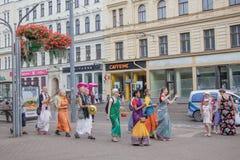Grupp av det hareKrishna folket som går och sjunger i gatorna av Riga royaltyfria foton