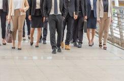 Grupp av det lyckliga unga affärslaget, businesspeople som tillsammans går det utomhus- kontoret arkivbild