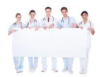 Grupp av doktorer med den tomma affischtavlan Royaltyfri Bild