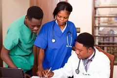Grupp av doktorer med minnestavladatorer som möter i medicinskt kontor royaltyfri fotografi