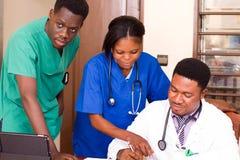 Grupp av doktorer med minnestavladatorer som möter i medicinskt kontor arkivfoton
