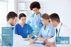 Grupp av doktorer med minnestavlaPC på sjukhuset Fotografering för Bildbyråer