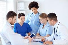 Grupp av doktorer med minnestavlaPC på sjukhuset Arkivfoton
